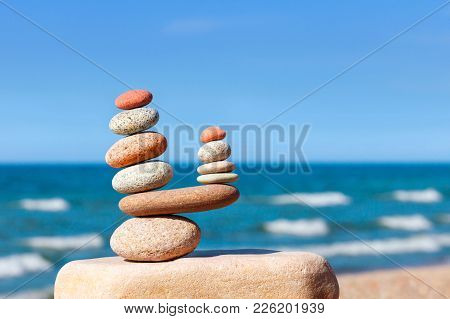 Two Pyramids Of Colored Balanced Rocks On A Background Of Blue Sky And Summer Sea. Concept Of Balanc