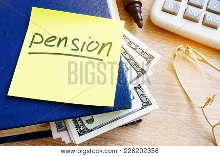 Pension Written On A Stick And Money In The Book. Retirement Savings.