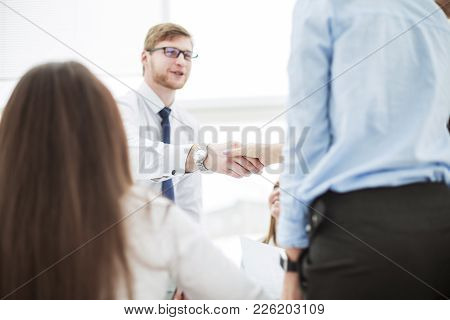 Bank Manager And The Customer Shake Hands After Signing A Lucrative Contract On The Background Of Th