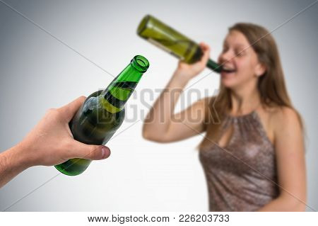 Unfocused Woman Drinking Alcohol And Hand Of Man With Beer On Gray Background