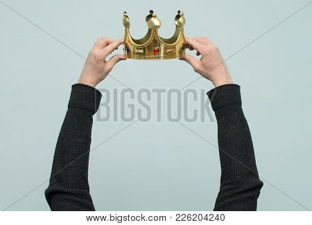 Hands Are Wearing A Golden Crown On Head Copy Space Isolated On Light Blue Background. Winner. Leade