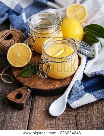 Lemon Curd In Glass Jar With Fresh Lemons
