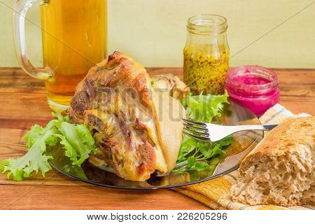 Baked Ham Hock On A Dark Glass Dish With Greens Abd Fork Closeup On Background Of Glass Mug With Bee