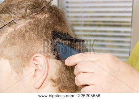 Lateral Part Of Head Of Young Man During Shearing By Means Of Electric Hair Clipper Closeup