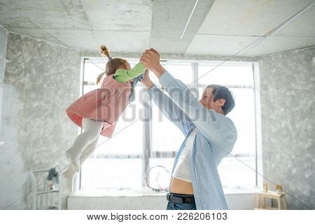 Dad Plays With His Little Daughter. The Man Lifts The Baby By The Handles. In His Eyes, Love And Ten