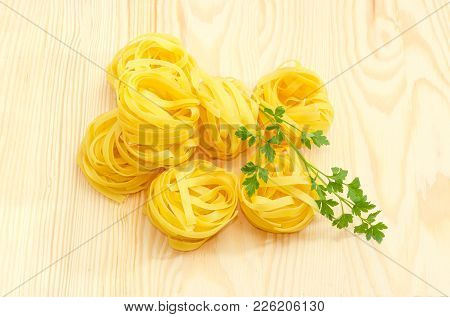 Several Uncooked Dried Noodle Nests With Parsley Twig On A Light Colored Wooden Surface