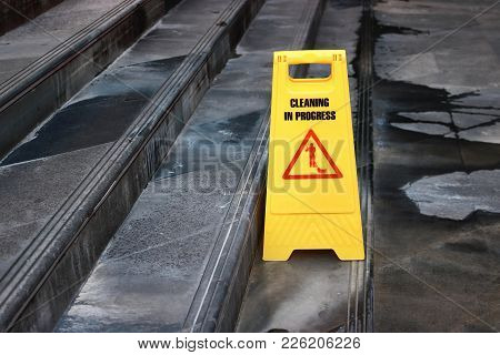 Yellow Caution Cleaning Progress Sign On The Floor Outdoors