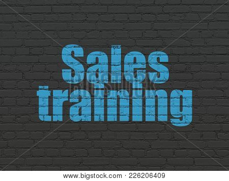 Advertising Concept: Painted Blue Text Sales Training On Black Brick Wall Background