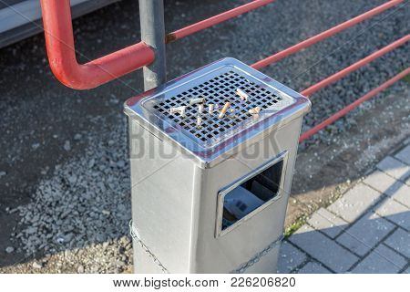 Street Trash Can With Ashtray And Cigarette Butts. Trash Can Tied To The Fence. Horizontal Photo
