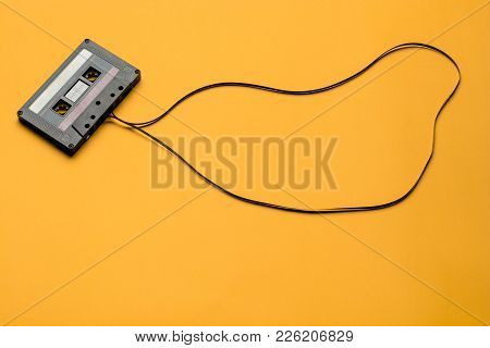 Retro Cassette Tape Over Orange Background. Top View. Copy Space.