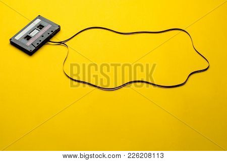Retro Cassette Tape Over Yellow Background. Top View. Copy Space.