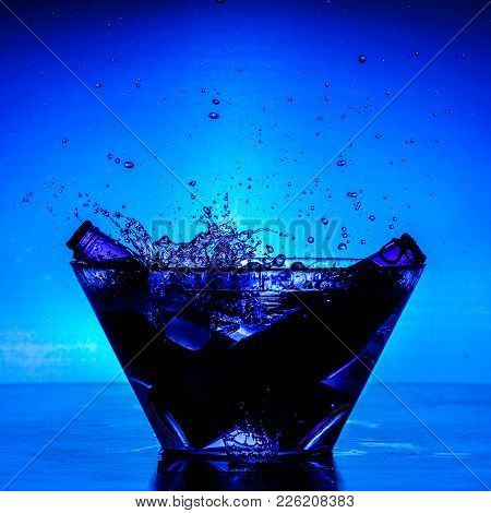 Cooling Bottles In Glass Bowl With Splashing Drops Of Water And Blue Background