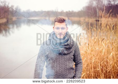 Portrait Of Handsome Man In Front Of Lake Surrounded By Fog