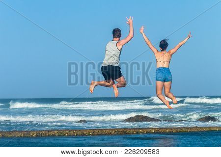 Girl Boy Teenagers Leaping Jumping Beach Ocean Tidal Swimming Pool Waves Holiday Landscape.