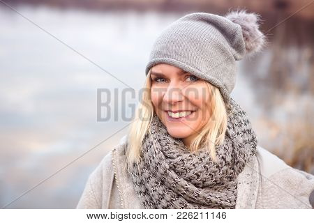 Portrait Of Beautiful Blond Woman In Front Of Lake