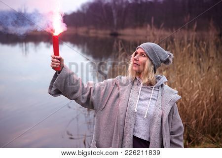 Woman Standing Outdoors In Front Of Lake With Burning Torch