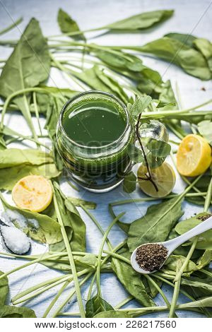 Juice Of Spinach,spinacia Oleracea Or Paalak With Sliced Lemons,citrus × Limon On  A Silver Wooden S