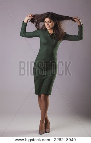 Young Brunette Woman In Green Dress Posing On Grey Background