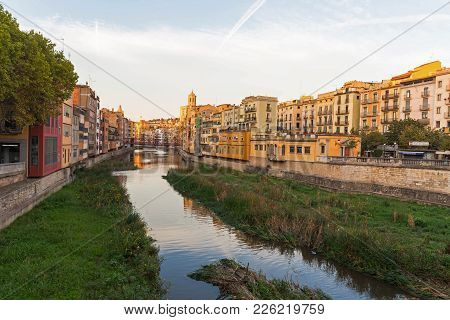 Girona, Spain - October 23, 2016: Onyar River Crossing The Downtown Of Girona With Bell Tower Of Bas