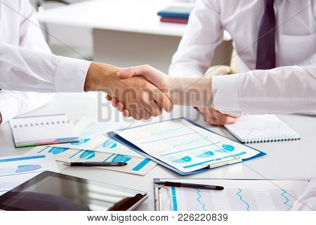 Close-up business people shaking hands in an office