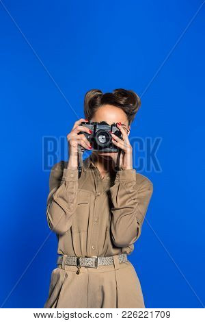 Obscured View Of Fashionable Young Woman In Retro Clothing With Photo Camera Isolated On Blue