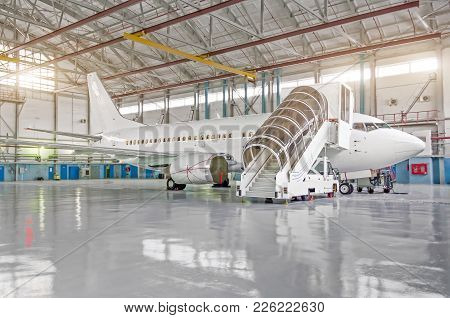 Passenger Airplane In The Hangar, Enclosed Engines And Gangway At The Entrance To The Aircraft