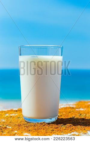 Glass Filled With Cow Milk Blue Sea And Sky