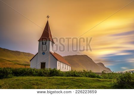 Sunrise Over The Lutheran Church  On A Mountain Top In The Town Of Vik In Iceland. Long Exposure.