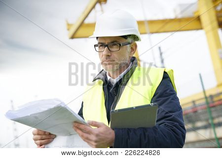 Construction manager on site reading blueprint