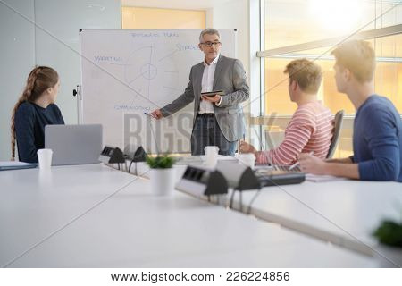 Economics teacher giving business class to students