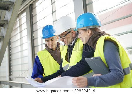 Construction site manager with young people in training period