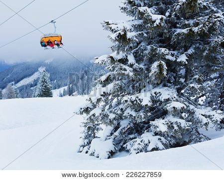 Chair Lift With Skiers At Alps Ski Resort