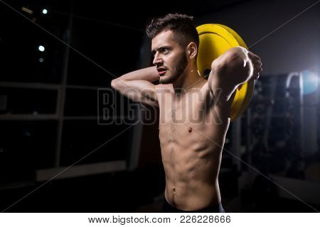 Sporty muscular man holding heavy barbell disc behind head while exercising in gym
