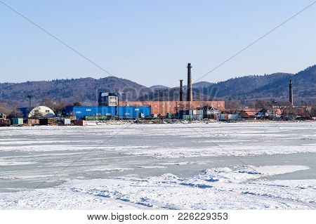 Industrial Area. Production Buildings. Pipes. View From The Frozen Sea In Winter. On Ice.