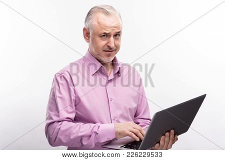 Do Not Think So. Grey-haired Senior Man Holding A Laptop And Frowning With A Doubting Expression Whi