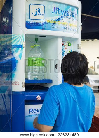 Bangkok, Thailand - June 29, 2015: A Woman Buying Fresh Water With Coin From Vending Machine In Bang
