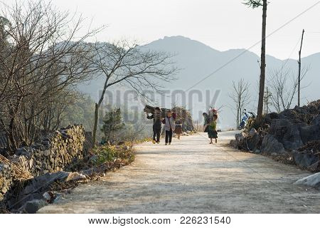 Ha Giang, Vietnam - Feb 14, 2016: Ha Giang Mountain View With Children Carry Wood On Back Heading Ho