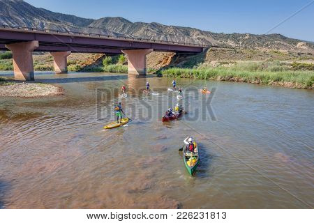 Dotsero, CO, USA  - August 19, 2012: Stand up paddleboards, kayaks and canoes in the annual Colorado River Race in the Glenwood Canyon.