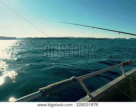 Trolling From A Boat. Sparkling Water Surface And Moving Fishing Rod