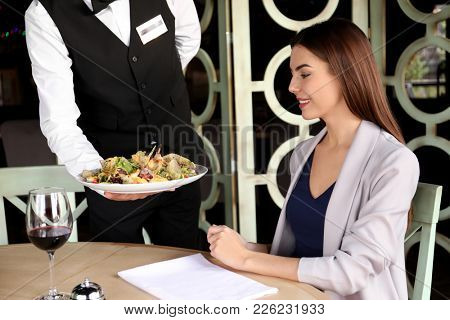 Waiter serving tasty salad at restaurant