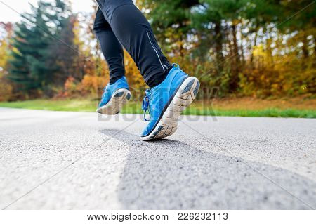 Unrecognizable Young Athlete In Blue Jacket Running Outside In Colorful Sunny Autumn Nature. Trail R
