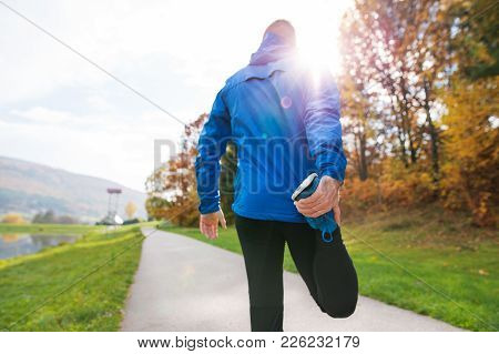 Young Runner In Blue Jacket Outside In Colorful Sunny Autumn Nature Standing On An Asphalt Path, Str
