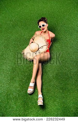 Overhead View Of Stylish Young Woman In Swimming Suit With Straw Hat Lying On Green Grass
