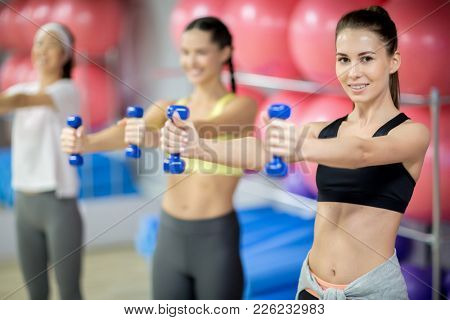 Row of young fit women working out with dumbbells altogether