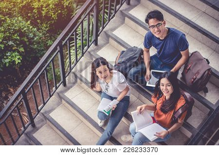 Three Asian Young Campus Students Enjoy Tutoring And Reading Books Together At Stair. Friendship And