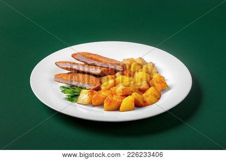 Schnitzel With Fried Potatoes On A White Plate On A Green Background. Side View. Garnished With Gree