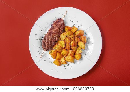 Meat Kebab From Pork, Beef With Fried Potatoes On A White Plate. Red Monophonic Background. A Hearty