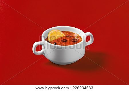 Solyanka With Olives, Olives And Lemon On A Monophonic Red Background In A Deep White Plate With Han