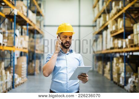 Warehouse Worker Or Supervisor With A Tablet And A Smartphone, Making A Phone Call.