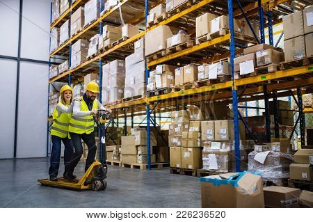 Two Young Workers In A Warehouse, Having A Ride On A Pallet Truck.